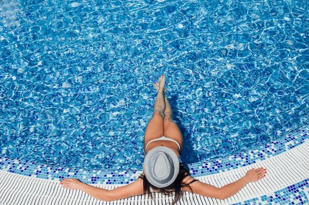 Een jong mooi meisje met een mooi figuur in een wit zwempak