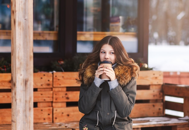 Een jong mooi meisje met een papieren kopje koffie zit op het open terras van het café