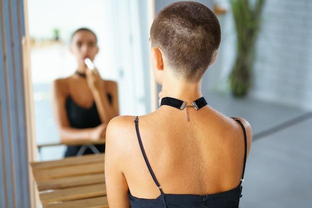 Een jong mooi meisje met kort haar schildert haar lippen, kijkend naar de weerspiegeling in de spiegel in zwarte kleding