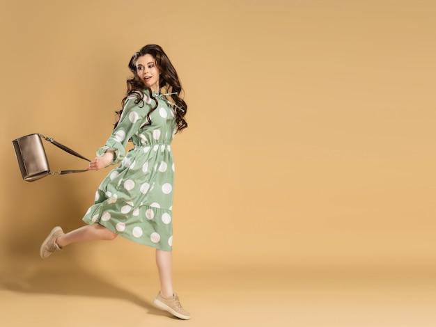 Een jong mooi meisje met lang krullend haar in een jurk met stippen springt met een tas in haar handen op een sinaasappel.