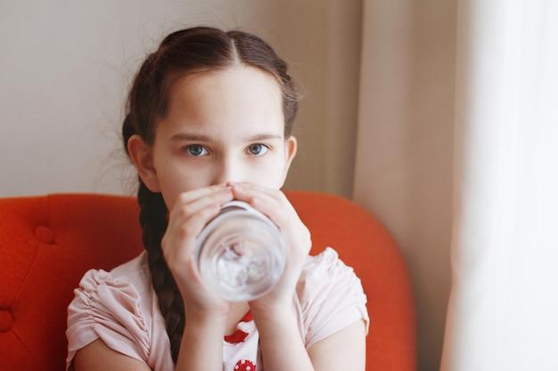 Een jong mooi meisje met vlechten drinkt water uit een fles.