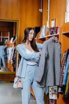 Een jong mooi meisje pakt kleren en gaat winkelen in de winkel.