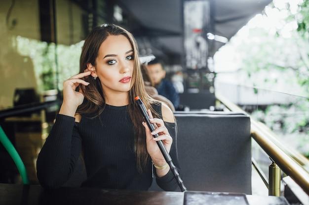 Een jong mooi meisje rookt waterpijp op het zomerterras van een modern restaurant.