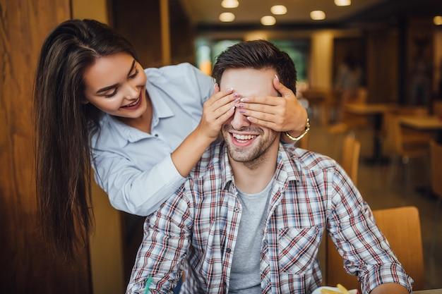 Een jong mooi meisje sluit het gezicht van haar vriendje achterin in restaurant