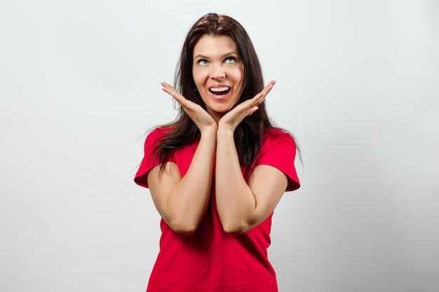 Een jong, mooi meisje toont een verrassing