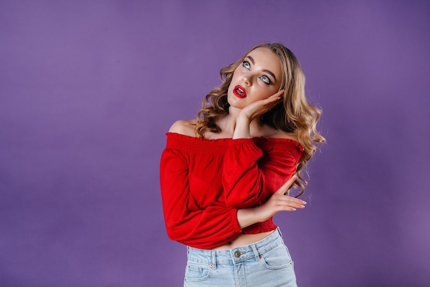 Een jong mooi meisje toont emoties en glimlacht in de studio op een paars