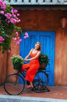 Een jong mooi meisje vormt zittend op een oude fiets met bloemen in een mand tegen de achtergrond van een oude muur. de decoratie van de tuin. vietnam