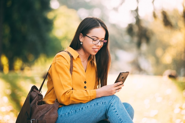 Een jong mooi meisje zit en zij kijkt en glimlacht in zijn telefoon buiten