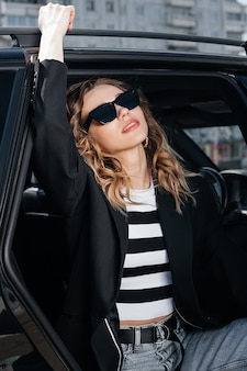 Een jong, mooi meisje zit op de achterbank van een auto. een stijlvol meisje in een pak en een bril stapt uit de auto.