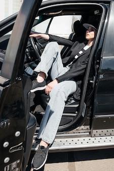 Een jong, mooi meisje zit op de bestuurdersstoel. een stijlvol meisje in een pak en een bril opent de autodeuren