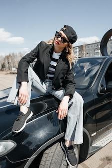 Een jong, mooi meisje zit op de motorkap van een auto. een stijlvol meisje in een pak en een bril op een zwarte auto.