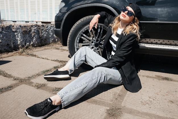 Een jong, mooi meisje zit op het asfalt in de buurt van haar zwarte auto in een zwarte jas, pet en bril.