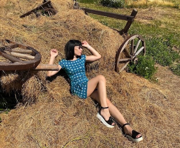 Een jong mooi meisje zit op het hooi van een omgevallen kar