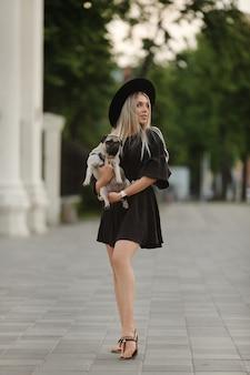 Een jong mooi model meisje in korte zomerjurk vreugdevol wandelen op een straat in de stad met haar kleine schattige hond.