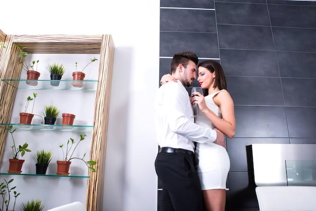 Een jong mooi paar dat in de woonkamer flirt.