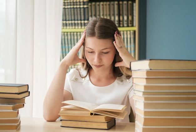 Een jong mooi studentenmeisje zit in de bibliotheek tussen enorme stapels boeken