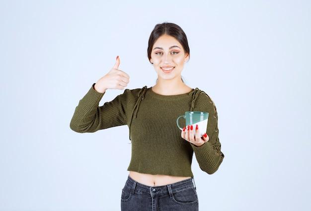 Een jong mooi vrouwenmodel dat een kop warme drank vasthoudt en een duim toont.