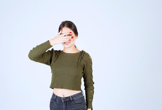 Een jong mooi vrouwenmodel dat haar gezicht op witte achtergrond verbergt