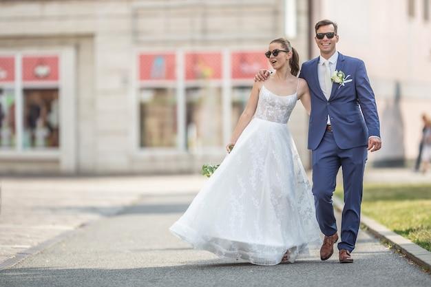 Een jong net getrouwd stel dat vrolijk door de stad loopt in trouwgewaden met een prachtig boeket.