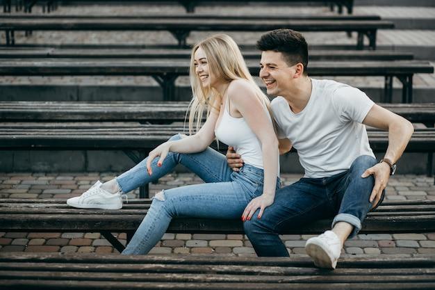 Een jong paar in liefde knuffelen op de bank in het park