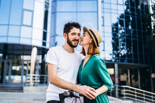 Een jong romantisch koppel met elektrische scooters op een date, wandelen in de stad. jonge vrouw in hoed en man geniet van een wandeling