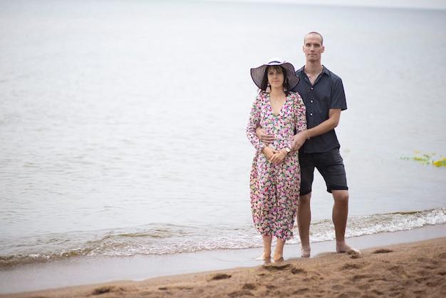 Een jong romantisch koppel staande op een zandstrand en staren naar de camera. verliefde paar in beach party