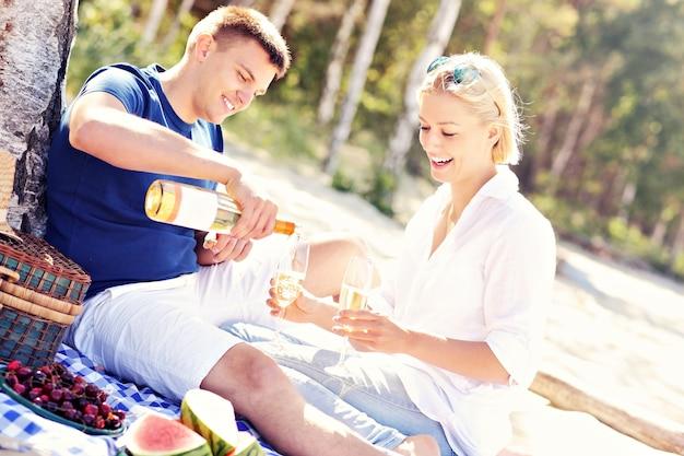 Een jong romantisch stel dat picknickt op het strand