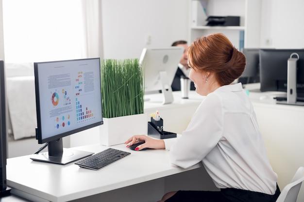 Een jong roodharig meisje zit achter de computer op kantoor en plant een werkschema. monitor mockup