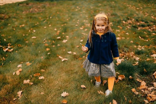 Een jong schattig meisje poseren in de herfst