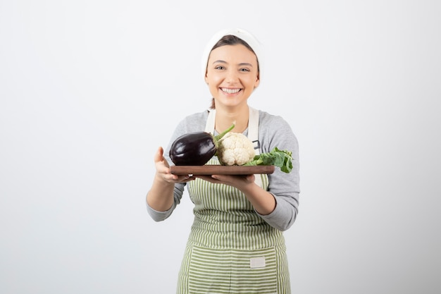 Een jong schattig vrouwenmodel met een houten bord met aubergine en bloemkool