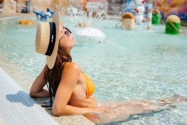 Een jong sexy meisje met een bril en een hoed lacht vrolijk tegen de achtergrond van een groot en modern waterpark op een zonnige dag. fijne vakantie vakantie. zomervakantie en toerisme.