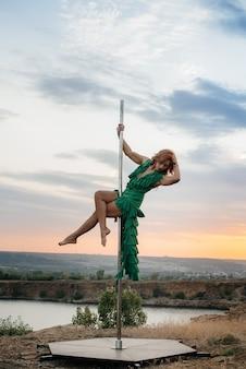 Een jong sexy meisje voert geweldige oefeningen op de paal uit tijdens een zonsondergang. dans. seksualiteit.