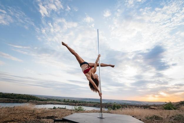 Een jong sexy meisje voert geweldige oefeningen uit op een paal tijdens een prachtige zonsondergang. dans. seksualiteit.
