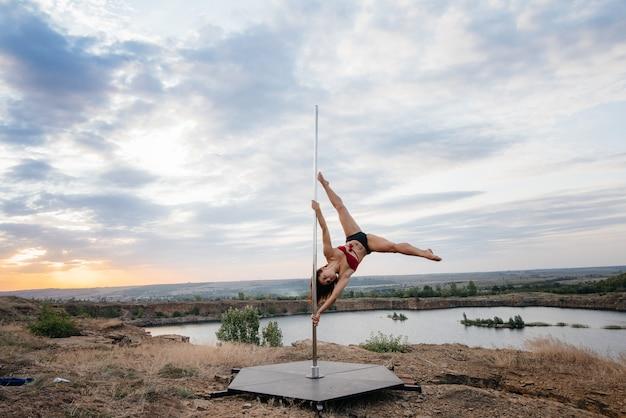 Een jong sexy meisje voert geweldige oefeningen uit op paal tijdens een prachtige zonsondergang. dans. seksualiteit.