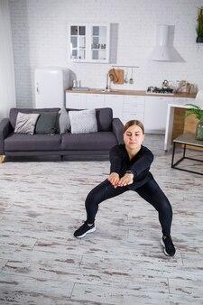 Een jong slank meisje gaat thuis sporten, ze is gekleed in fitnesskleding, een zwarte top en een legging. thuis fitnessen voor een mooi lichaam