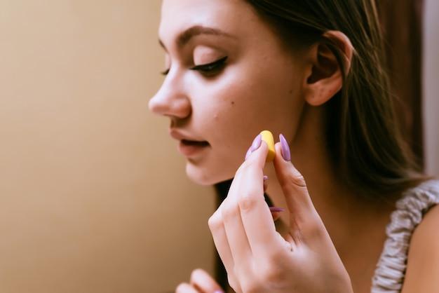 Een jong slaperig meisje wil slapen, doet gele oordopjes in haar oren tegen straatlawaai