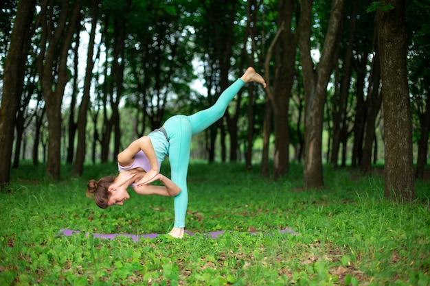 Een jong sportmeisje beoefent yoga in een opgehouden groen zomerbos