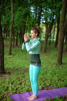 Een jong sportmeisje beoefent yoga in een rustig groen zomerbos, yoga verzekert houding. meditatie en eenheid met de natuur