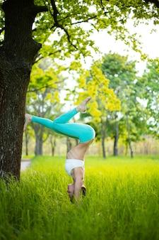 Een jong sportmeisje beoefent yoga in een rustig groen zomerbos