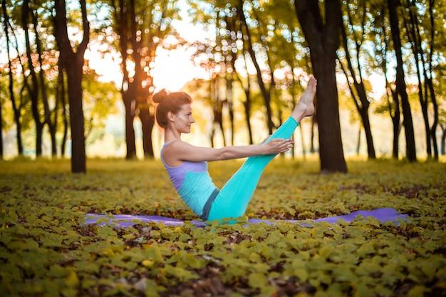 Een jong sportmeisje beoefent yoga in een stil groen bos in de herfst bij zonsondergang, in een yogaasana. meditatie en eenheid met de natuur