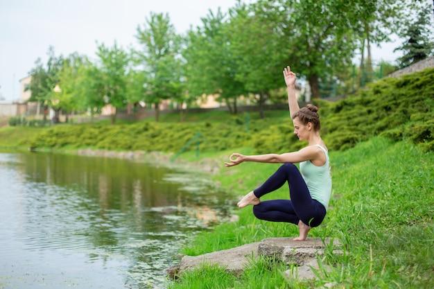 Een jong sportmeisje beoefent yoga op een groen gazon bij de rivier