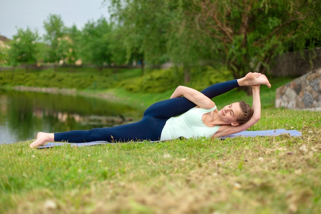 Een jong sportmeisje beoefent yoga op een groen grasveld bij de rivier, yoga verzekert houding.