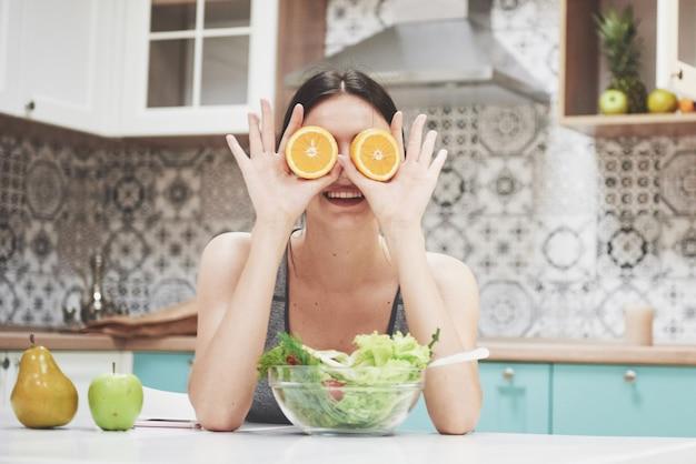 Een jong sportmeisje geniet van een fruitsalade. speels zijn en haar ogen bedekken met oranje.
