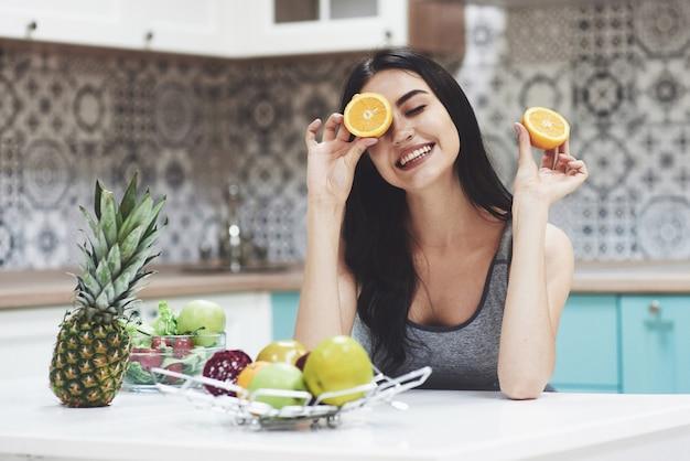 Een jong sportmeisje geniet van een fruitsalade. speels zijn en haar ogen bedekken met oranje