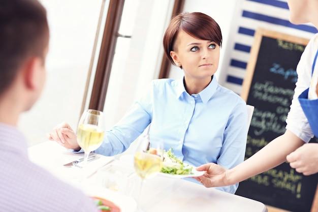 Een jong stel dat in een restaurant zit en bediend wordt