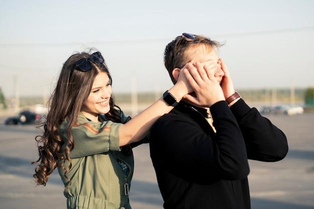 Een jong stel familie bedekt ogen en verrast buitenshuis, gelukkig romantisch liefde concept