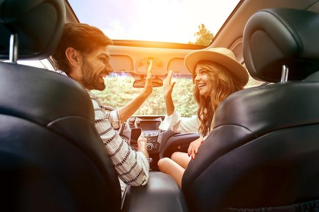 Een jong stel geeft vijf aan elkaar in een nieuwe auto. een man die een auto bestuurt met zijn vriendin en plezier heeft. een auto kopen en huren. reizen, toerisme, recreatie.