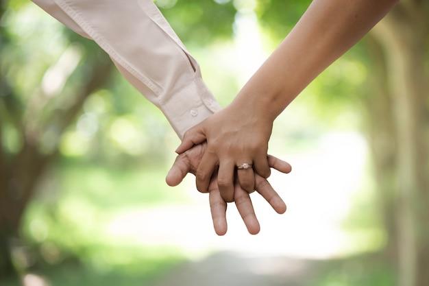 Een jong stel hand in hand in het park thailand