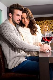 Een jong stel heeft een romantische avond met een glas wijn thuis in de woonkamer.