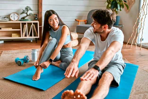 Een jong stel in sportkleding doet thuis oefeningen op matten in een lichte, gezellige woonkamer. gezonde levensstijl, sport, yoga, fitness.